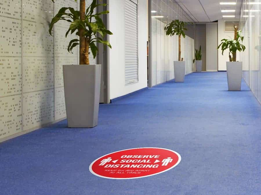 "Social Distancing Sticker for Carpet Tiles that says ""Observe Social Distancing"" in an office hallway"
