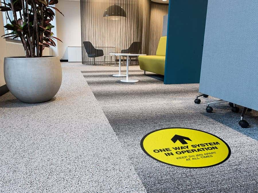 "Social Distancing Sticker for Carpet Tiles that says ""One Way System in Operation"" in an office"