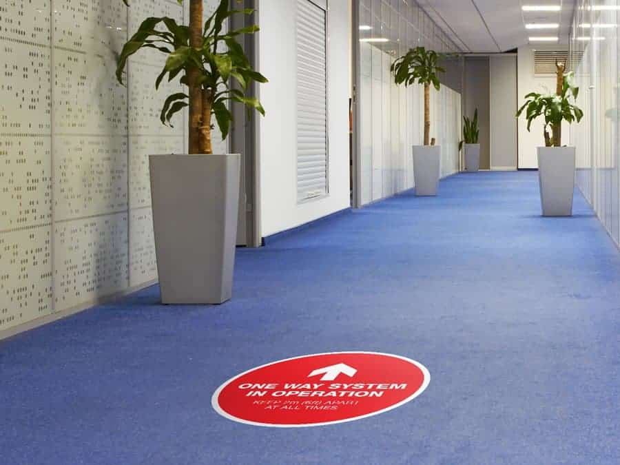 "Social Distancing Sticker for Carpet Tiles that says ""One Way System in Operation"" in an office hallway"