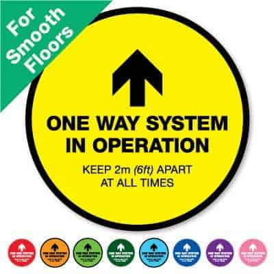 "Round yellow Social Distancing Sticker for smooth floors that says ""One Way System in Operation"" on the top plus 8 other colours o the bottom"