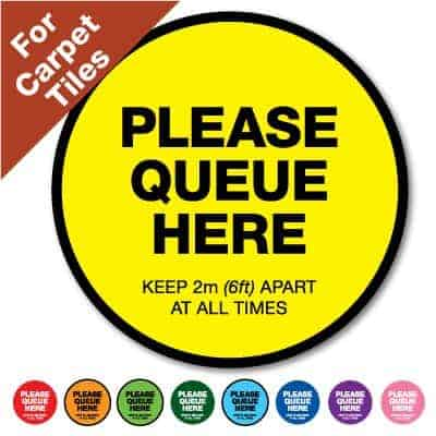 "Round yellow Social Distancing Sticker for carpet tiles that says ""Please Queue here"" on the top plus 8 other colours o the bottom"