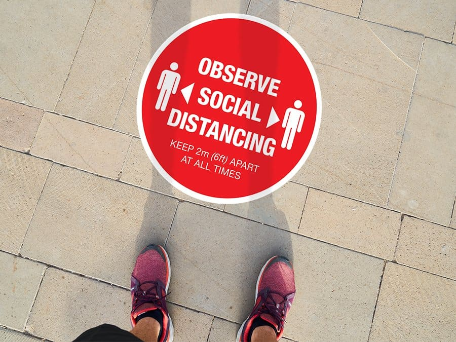 "Social Distancing Sticker for outdoor usage that says ""Observe Social Distancing"" on a paved ground"