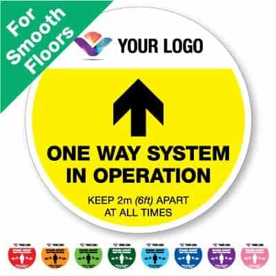 "Round yellow Social Distancing Sticker for smooth floors branded with a logo that says ""One Way System"" on the top plus 8 other colours o the bottom"