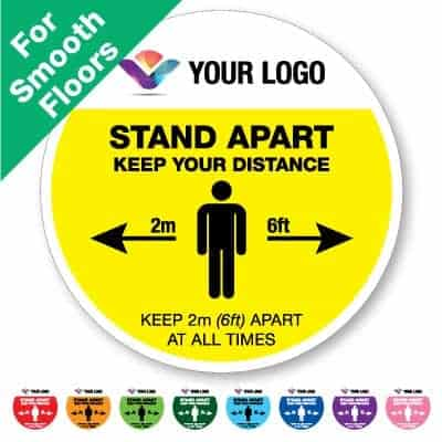 "Round yellow Social Distancing Sticker for smooth floors branded with a logo that says ""stand apart keep your distance"" on the top plus 8 other colours o the bottom"