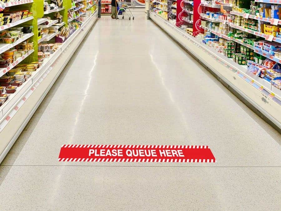 "Rectangular social distancing sticker in red and white with the words ""please queue here"", on a supermarket floor"